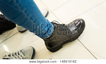 girl measures the new shoes. She stamps her black boots