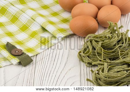 Raw green Italian pasta on old wooden table. Selective focus.