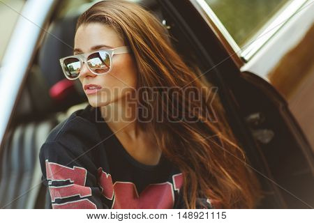 Brunette in sunglasses sitting in burgundy car, tinted photo