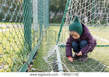 Little girl playing on a fooball pitch. She is sitting behind the goal.