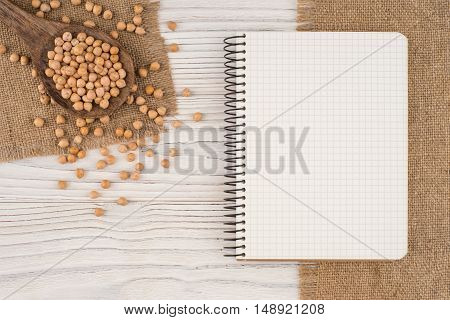 Chickpeas in a wooden spoon on old wooden table. Top view.