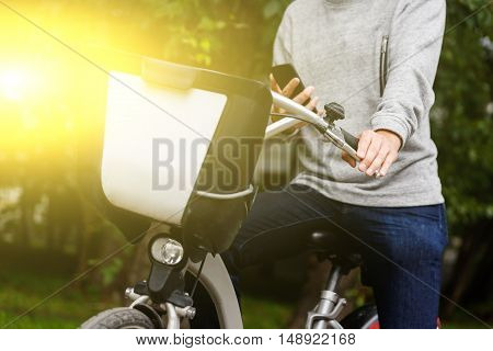Man in casual clothing sitting on his bike with mobile phone in green area. Image with lens flare effect