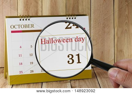 Magnifying glass in hand on calendar you can look Halloween Day on 31 October concept of a public relations campaign activities in Halloween Day.