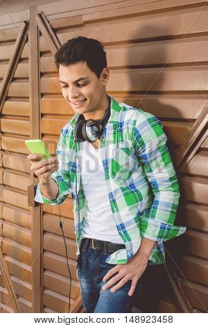Cool millennial young man with smart phone and headphones smiling. Portrait of handsome hipster teenage guy using smart phone outdoors. No retouch.