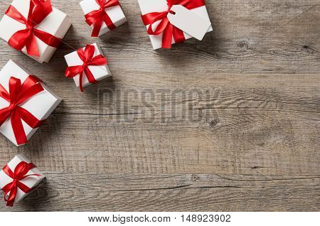 Top view of white gift boxes wrapped with red ribbon. High angle view of presents on wooden table. Christmas or valentine gift box with copy space on rustic table.
