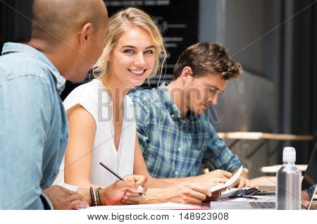 Close up of young woman looking at camera while her friends studying. Team of students preparing for university exam. Portrait of beautiful girl with her friends studying outdoor in a summer day.