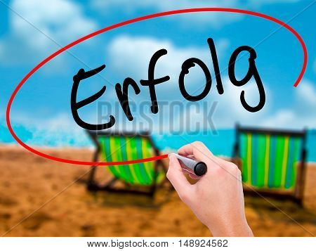 Man Hand Writing Erfolg Success (in German) With Black Marker On Visual Screen
