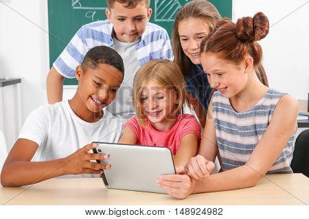 Schoolchildren with tablet computer in classroom