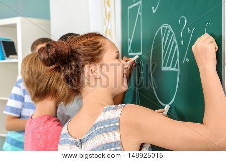 Schoolchildren in classroom writing on blackboard