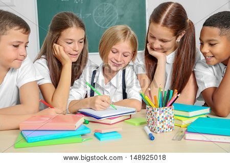 Schoolchildren drawing while sitting at table in classroom