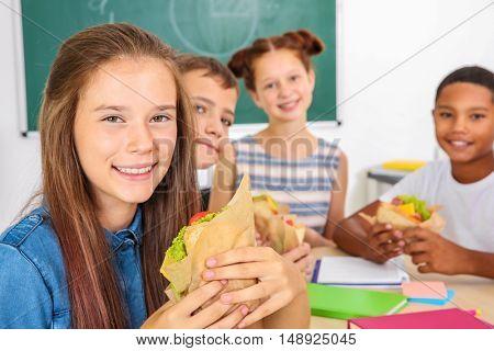 Portrait of schoolgirl having lunch in classroom