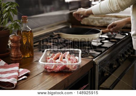 A man adding salt to a hot pan about to grill steak in the kitchen with oil, pepper and basil on the table