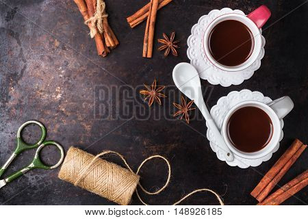 Hot chocolate in a mug with spices on grunge dark table. Selective focus, tasty holidays concept. Drink for fall and winter. Copy space background, top view overhead flat lay