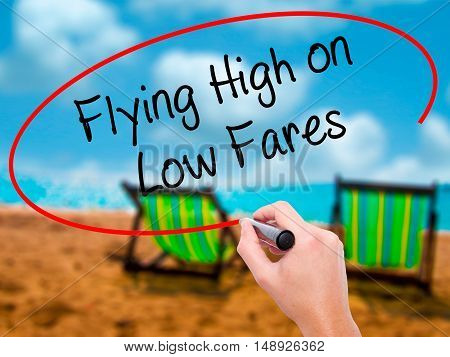 Man Hand Writing Flying High On Low Fares With Black Marker On Visual Screen