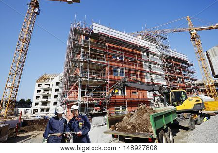 two construction workers inside large building industry construction blocks of apartments