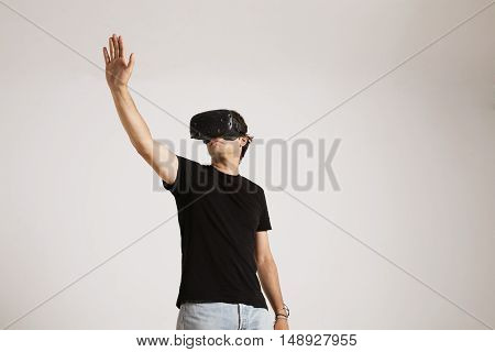 Low angle shot of a young caucasian model in jeans and unlabeled black t-shirt reaching out his hand while playing in VR glasses against white wall background.