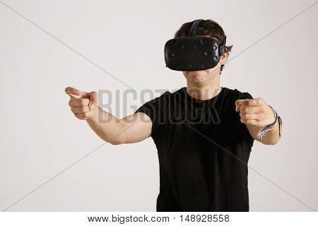 Focused serious young gamer in black t-shirt and VR glasses stretching his hands out as if driving, isolated on white