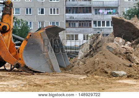 The process of demolition. Bucket Excavator with construction debris. Panel multistory building in the background.