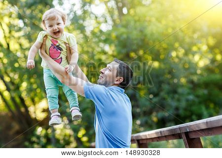Dad holds baby daughter in his arms in summer park.Image with lens flare effect
