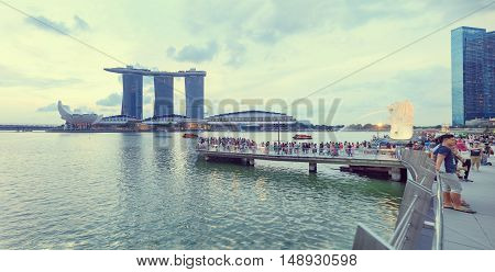 Singapore, Republic of Singapore - May 6, 2016: Crowds of tourists admire the view of Marina Bay Sands hotel, ArtScience museum and Flyer near Merlion sculpture