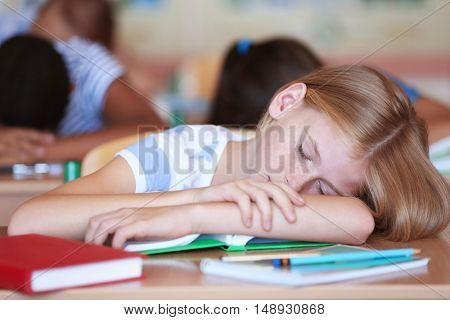 Tired schoolgirl in classroom on lesson