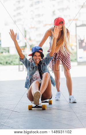 one blonde woman riding other brunette on longboard