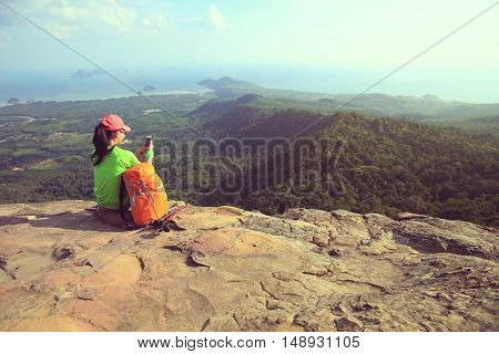 young woman hiker taking photo with smartphone on mountain peak cliff