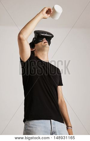 A man in blank black t-shirt and VR headset is looking up into an empty white mug he holds above his head, isolated on white
