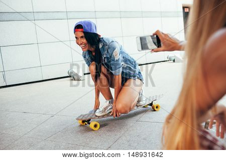 one blonde woman shooting other brunette on longboard