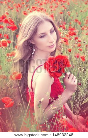 Young Woman With Long Blonde Hair In A Red Dress Holding A Bouquet Of Flowers In A Poppy Field. Past