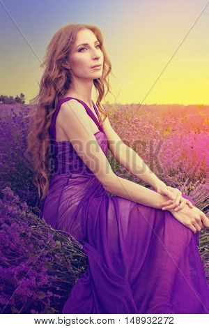 Young Woman With Long Blonde Hair In A Purple Dress Looking At The Sunset In A Warm Summer Day In Th