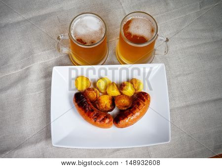 Pork sausages on a white plate mugs of beer roasted potatoes. Top view