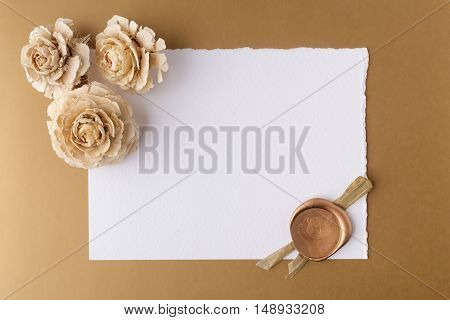 Letter with wax seal and dry roses on golden background. Flat lay. Owerhad view