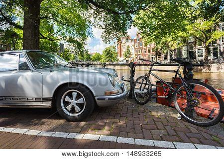 Amsterdam Netherlands - July 03 2016: Porsche 911S parked on a street of Amsterdam sunny day