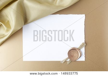 Satin on golden background with blank paper. Flat lay. Owerhad view