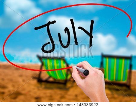 Man Hand Writing July With Black Marker On Visual Screen