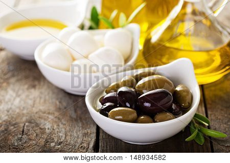 Olive oil in vintage bottle with black and green olives and fresh mozzarella cheese on rustic wooden background