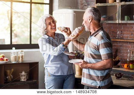 Happy aging. Nice classy man and woman feeding each other with cruassans and laughing