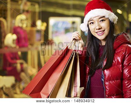 happy young asian woman wearing christmas hat carrying shopping bags