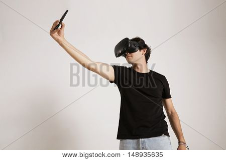 A young model in unlabeled black t-shirt, jeans and VR headset trying to take a selfie on his smartphone