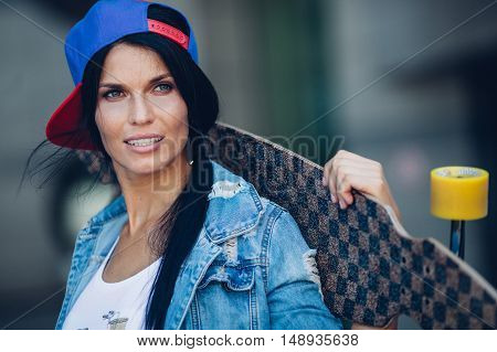 yong brunette woman holding longboard behind head, closeup portrait