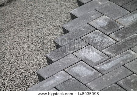 Gray concrete bricks  and little stones building a floor