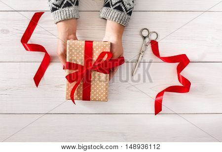 DIY hobby. Woman's hands give wrapped christmas or other holiday handmade present in paper with red ribbon. Present box, decoration of gift on white wooden table, top view with copy space