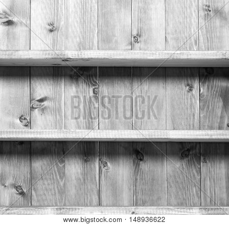 Old grey empty book sheves on wooden wall.