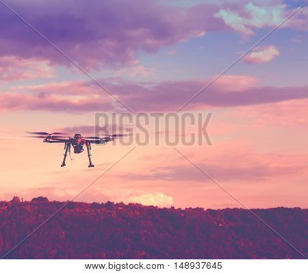 Silhouette Of Drone Hovering In A Colorful Sunset. Toned Image. Soft Focus