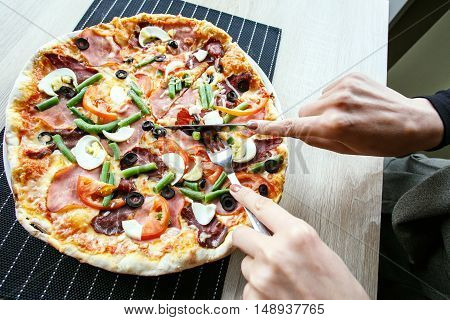 woman hands Slicing fresh pizza with beans, cheese, ham, eggs, pepperoni and vegetables. Cutting pizza