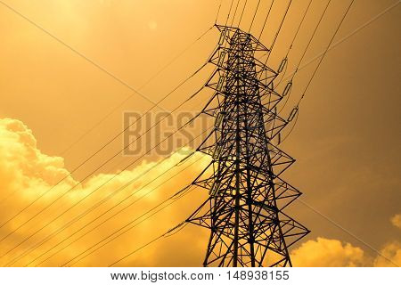 Electrical high voltage pole and cloudy sky in evening time