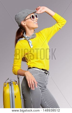 Lovely woman in a grey hat with suitcase against isolated background