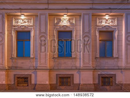 St. Petersburg Russia - August 4 2016: Three windows in a row on night illuminated facade of the Institute of Oriental Manuscripts front view