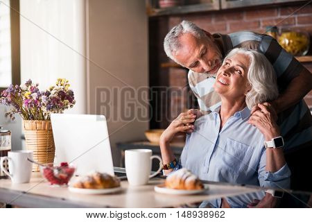 Happy family. Attractive aged female working at kitchen table while her husband approaching her